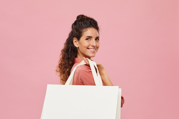 Портрет счастливой молодой женщины, улыбающейся и держащей белый бумажный пакет, изолированного на розовом фоне