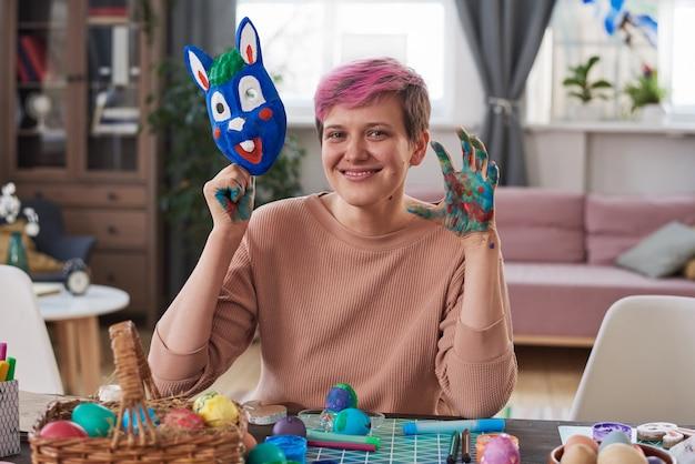 Портрет счастливой молодой женщины, улыбающейся в камеру, сидя за столом во время занятий по искусству