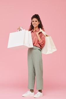 彼女が買い物に満足した買い物袋を立って保持している幸せな若い女性の肖像画