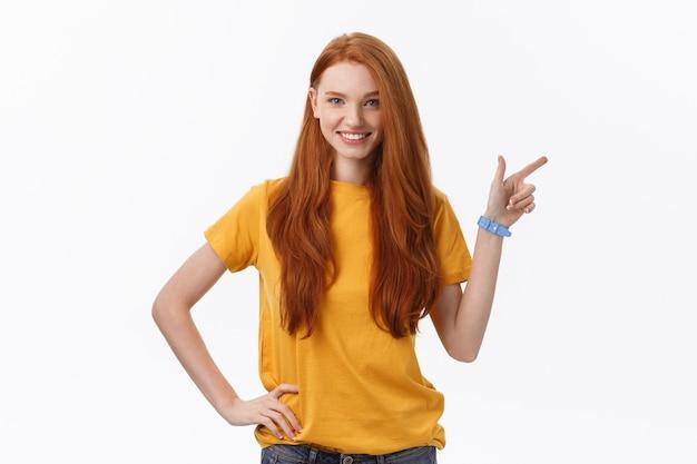 白い壁の上に孤立して立っている幸せな若い女性の肖像画