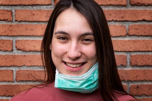 의료 마스크를 쓰고 행복 한 젊은 여자의 초상화입니다. 코로나 바이러스 개념