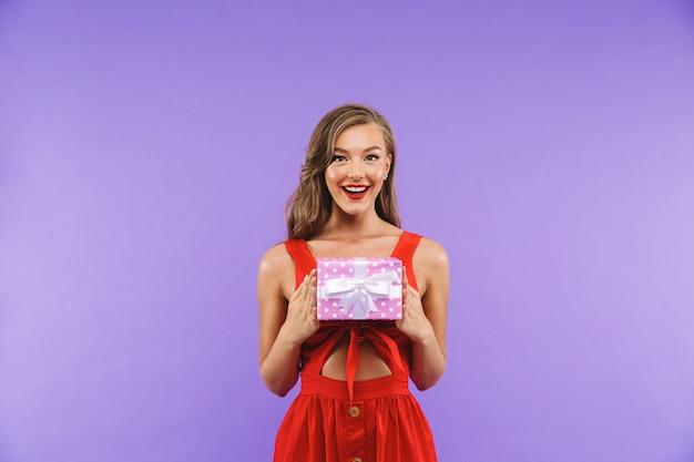 웃 고 선물 상자를 들고 빨간 드레스를 입고 행복 한 젊은 여자의 초상화 서