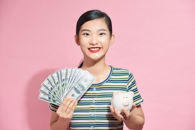 ピンクのお金と貯金箱を持つ幸せな若い女性の肖像画