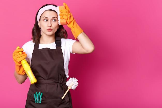오렌지 스폰지와 세제 손에 행복 한 젊은 여자의 초상화 손 보호 및 분홍색 앞치마, 분홍색 벽 위에 절연 주황색 고무 장갑을 끼고 그녀의 집을 청소합니다. 공간을 복사하십시오.