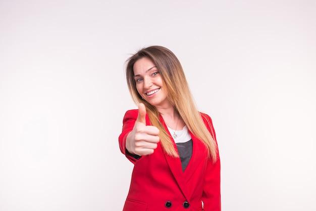 スタジオで赤いジャケットに親指を立てて幸せな若い女性の肖像画