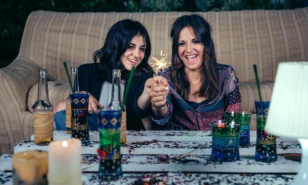 屋外の夜のパーティーで線香花火を笑って保持している幸せな若い女性の友人の肖像画。線香花火に選択的に焦点を当てます。