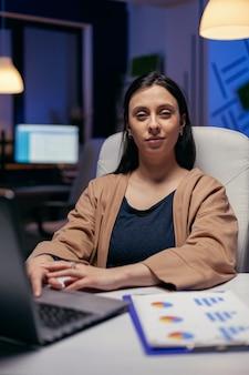 초과 근무를 하는 카메라를 바라보는 열심히 일하는 관리자의 초상화. 그녀의 일을 하는 늦은 밤 시간에 그녀의 직장에 앉아 똑똑한 여자.