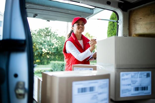 Портрет трудолюбивой женщины-курьера, расставляющей посылки перед доставкой.