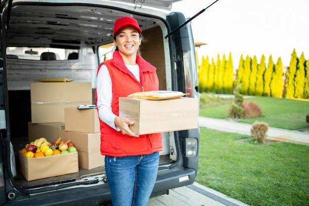 Портрет трудолюбивого женского курьера, держащего пакет перед доставкой.