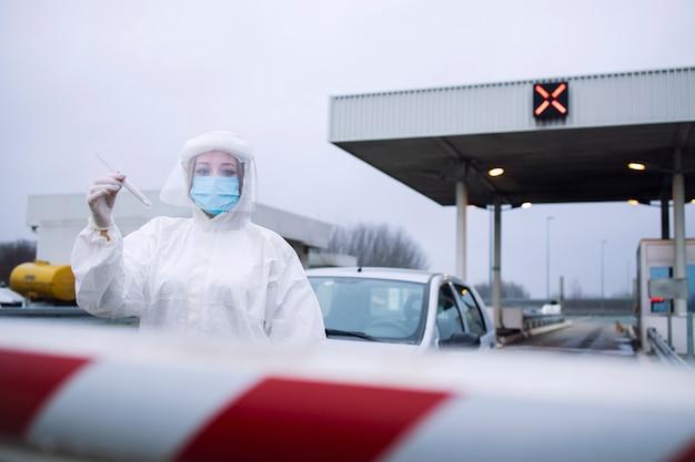 Портрет медицинского работника в белом защитном костюме, стоящего на контрольно-пропускном пункте для проведения пцр-теста пассажиров из-за пандемии вируса короны.
