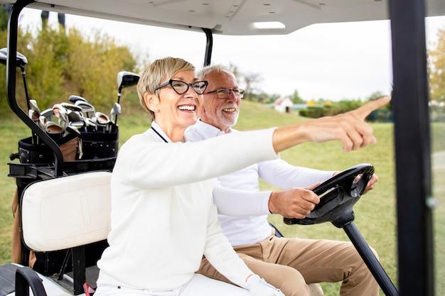 Портрет здоровой активной старшей пары за рулем автомобиля для гольфа и наслаждаясь свободным временем на открытом воздухе.