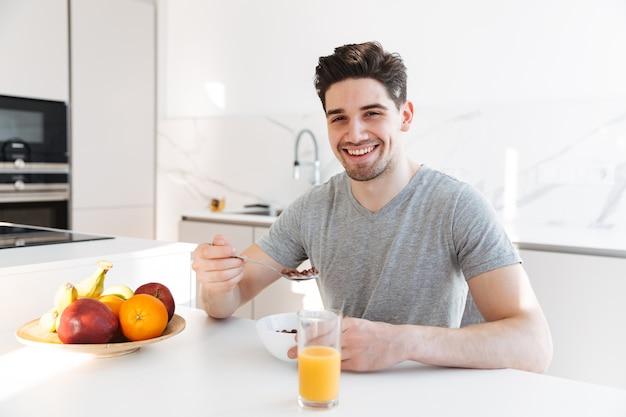 Портрет здорового взрослого человека в повседневной футболке, улыбаясь и с вегетарианским завтраком в квартире