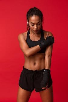 Портрет здоровой афро-американской женщины 20 лет в черной спортивной одежде, стоящей со спортивными повязками на руках, изолированной над красной стеной