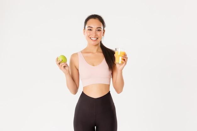 Портрет здоровой и подходящей симпатичной азиатской спортсменки, держащей апельсиновый сок и яблоко, утренний завтрак перед тренировкой, белый фон.