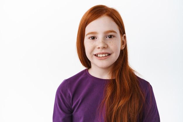 Портрет здоровой и счастливой рыжей маленькой девочки с веснушками, улыбающейся зубами и радостной спереди