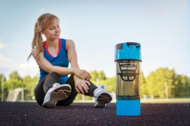 Портрет здоровой девушки фитнеса выпивая протеиновый коктейль во время тренировки на стадионе. девушка отдыхает на стадионе после бега. отдыхать после утренней пробежки