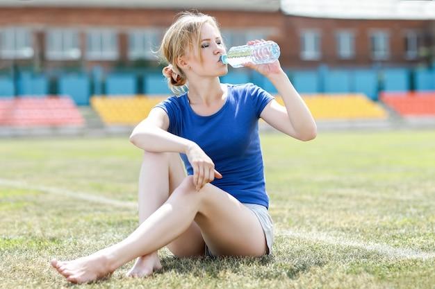 水を飲む健康なフィットネスの女の子の肖像画。運動中にスポーツ栄養飲料を飲む女性。