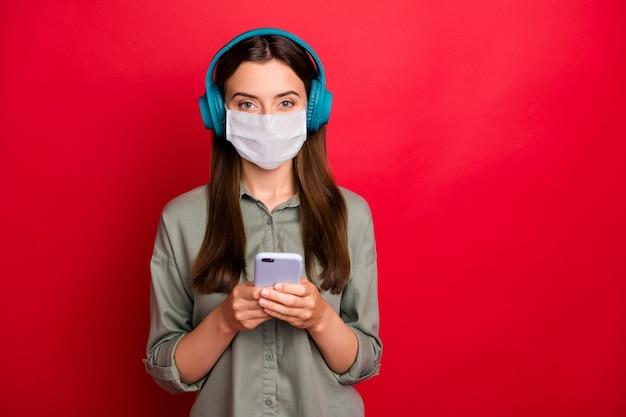 ヒットラジオプレイリストを聞いて安全マスクを身に着けている健康な女の子の肖像画は家にいる