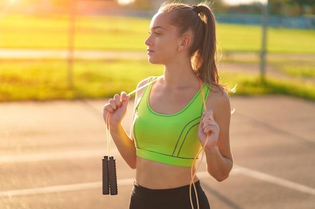 屋外で縄跳びで健康的なスポーツウーマンの肖像画。体調を整え、スポーツライフスタイルを持つ