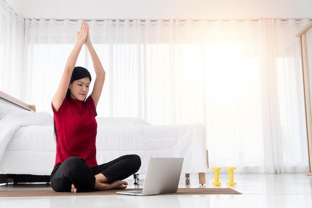 寝室に座って、自宅のラップトップでオンラインで学ぶヨガの練習を練習している健康な若いアジアの女性の肖像画。運動とリラクゼーションの概念、新しい通常のライフスタイルのためのテクノロジー