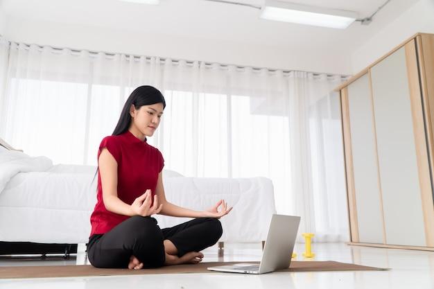 寝室に座ってヨガの練習を練習している健康な若いアジアの女性の肖像画