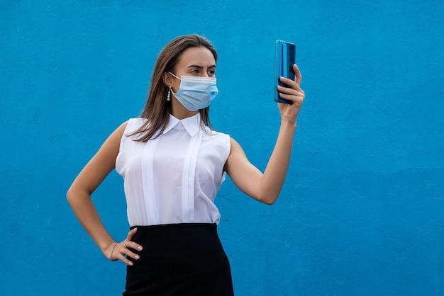 青い背景に携帯電話と医療マスクを身に着けている健康な若いビジネス女性の肖像画。 covid19による2020年のコンセプト