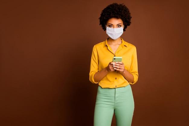 Портрет ее привлекательной здоровой девушки в марлевой маске безопасности, использующей устройство, читать, просматривать информацию, новости, вирусная пневмония, загрязнение воздуха, co2, китай, ухань, проблема, mers cov, изолированный коричневый цвет фона
