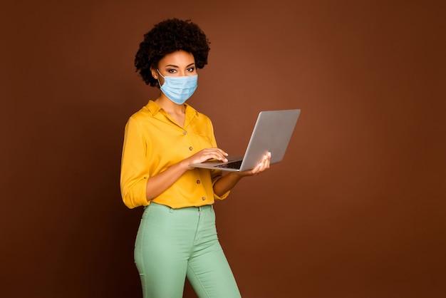 Портрет ее привлекательной здоровой девушки в марлевой маске безопасности, использующей ноутбук, самоизоляцию, оставайся дома, коворкинг, стоп, mers cov, грипп, грипп, грипп, грипп, изолированный коричневый цвет фона