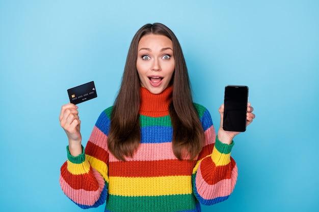 그녀의 초상화는 손에 가제트 은행 카드 클라이언트 서비스 전자 뱅킹 판매 할인 클럽 프로모션을 들고 있는 매력적인 사랑스럽고 경쾌한 소녀의 초상화가 밝고 생생한 선명한 파란색 배경을 격리하고 있습니다.