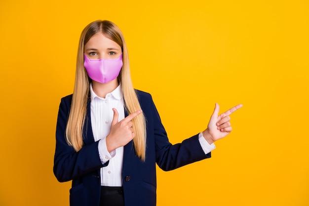 Портрет ее длинноволосого здорового школьника в безопасной розовой текстильной многоразовой маске, демонстрирующей копирование пространства для предотвращения заражения вирусом изолированного яркого яркого блеска на ярком желтом цветном фоне