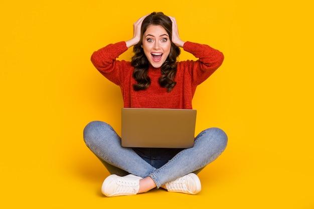 그녀의 초상화는 밝고 선명한 노란색 배경에 격리된 노트북 행운의 뉴스 복권 당첨을 사용하여 앉아 있는 밝고 쾌활한 운이 좋은 물결 모양의 머리 소녀를 놀라게 했습니다.