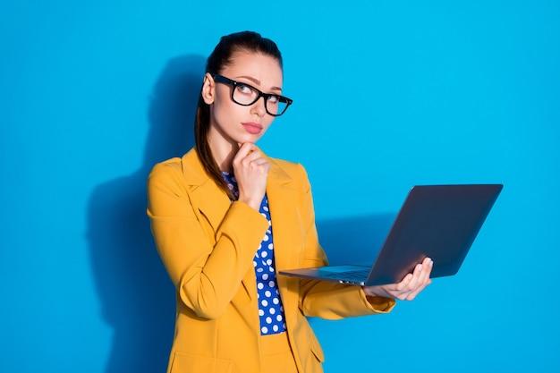 그녀의 초상화는 매력적인 매력적인 세련되고 창의적인 생각을 가진 여성 리더가 손에 노트북을 들고 재무 계획을 생각하고 밝고 선명한 파란색 배경을 가지고 있습니다.