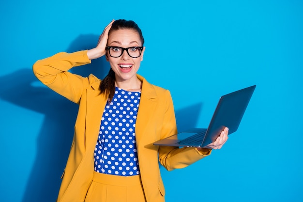 彼女の肖像画彼女は素敵な魅力的な魅力的なシックなスマート賢い陽気な陽気な嬉しい女性を手に持ってラップトップを勉強している学習ウェブ分離された明るい鮮やかな輝き鮮やかな青い色の背景
