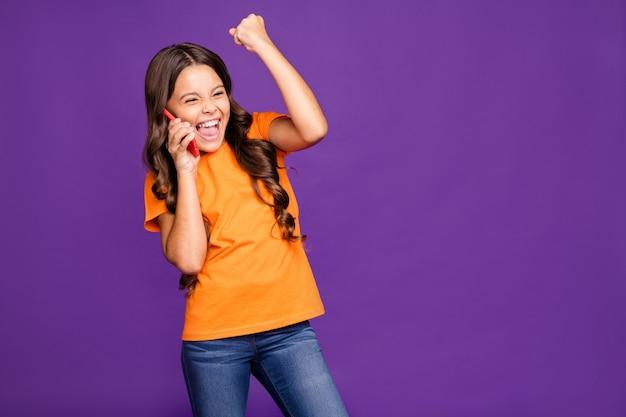 Портрет ее милая привлекательная очаровательная прекрасная веселая радостная довольная с волнистыми волосами девушка разговаривает по телефону, празднуя изолированную на ярком ярком сиянии, ярком лиловом фиолетовом фиолетовом цветном фоне