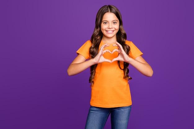 Портрет ее она милая привлекательная очаровательная милая милая милая добрая веселая волнистая девушка, показывающая знак сердца, изолированные на ярком ярком блеске ярком лиловом фиолетовом фиолетовом цветном фоне