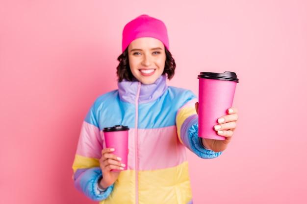 그녀의 초상화 그녀는 핑크 파스텔 배경 위에 절연 당신에게주는 녹색 허브 차의 손에 두 테이크 아웃 컵을 들고 좋은 매력적인 쾌활한 명랑 소녀