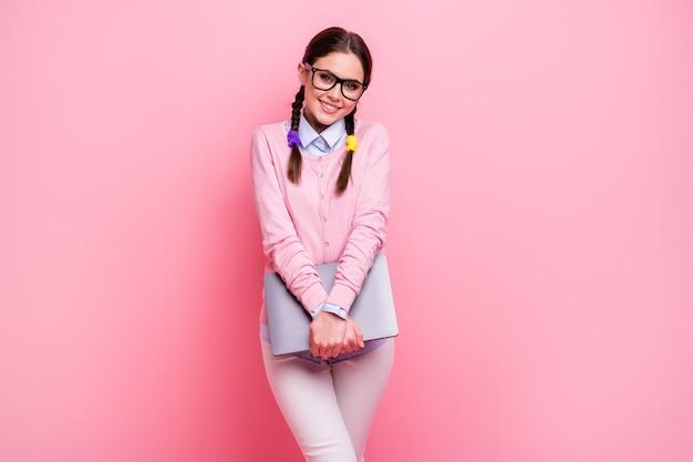 그녀의 초상화는 분홍색 파스텔 색상 배경에서 원격으로 격리된 노트북 학습 주제를 사용하여 손을 잡고 있는 멋지고 밝고 쾌활한 겸손한 갈색 머리 10대 소녀의 초상화
