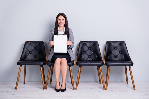 그녀의 초상화는 서류 보험 연락 고객 지원을 들고 의자에 앉아 있는 멋지고 쾌활하고 자신감 있는 성공적인 여성 임원 관리자가 격리된 파스텔 회색 배경입니다.