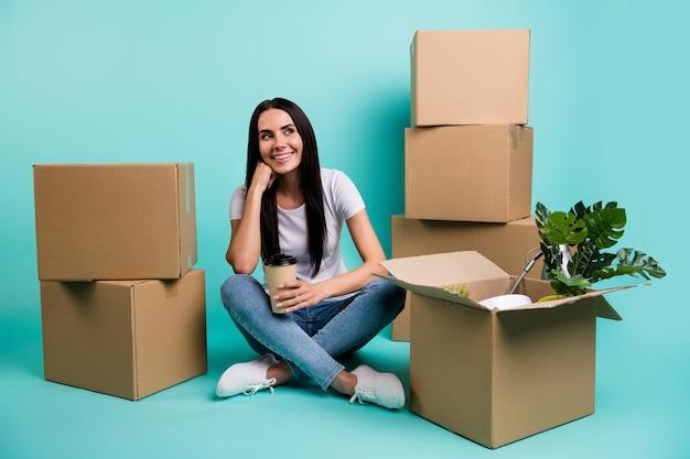 Портрет ее красивой привлекательной веселой мечтательной брюнетки, переезжающей за границу, сидя на полу с кучей коробок