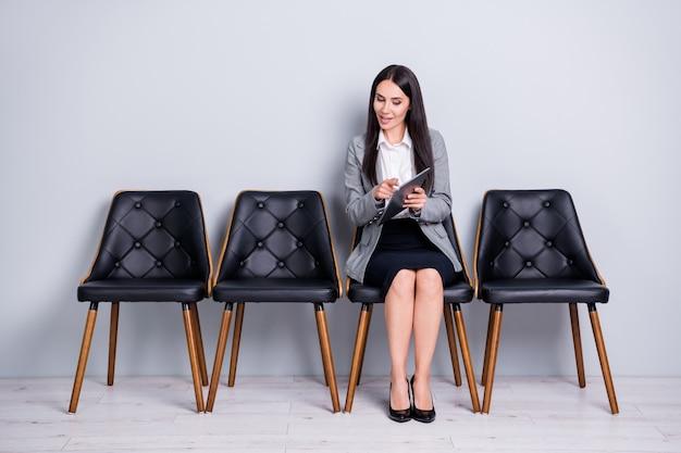 그녀의 초상화는 매력적인 밝고 친근한 자신감 있는 여성 부동산 중개인 금융가 마케터 앉아 의자에 앉아 인덱스 비율 투자를 보여주는 전자책 가제트를 보여주는 파스텔 회색 배경을 보여줍니다.