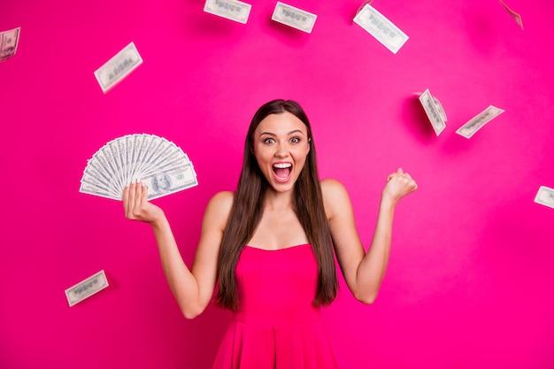彼女の肖像画彼女は明るい鮮やかな輝き鮮やかなピンクのフクシア色の背景に分離された大きな金額の予算の外貨両替を手に持っている素敵な魅力的な陽気な嬉しい成功した長髪の女の子