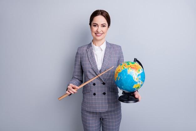 Портрет ее красивой привлекательной веселой интеллектуальной наставницы в клетчатом костюме, держащей в руке земной шар, демонстрирующей карту страны, экологию климата планеты, изолированную на сером пастельном цветном фоне