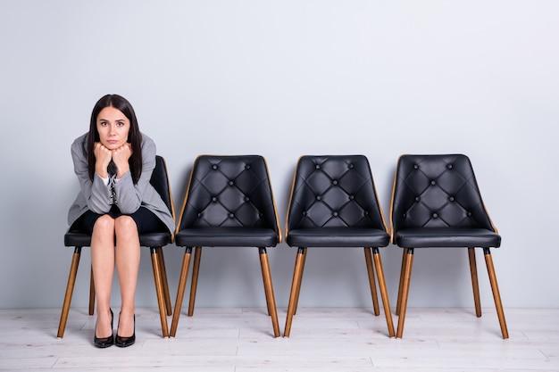 彼女の肖像画彼女は素敵な魅力的な上品で退屈な熟練した女性のセールスエグゼクティブマネージャーが椅子に座って会議のリクルーターを待っている孤立したパステルグレーの色の背景を適用します