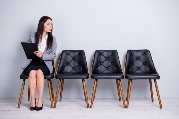 그녀의 멋진 매력적이고 호기심 많은 여성 임원 매니저가 의자에 앉아 계약서에 서명하기를 기다리고 고립된 파스텔 회색 배경을 엿보고 있는 모습