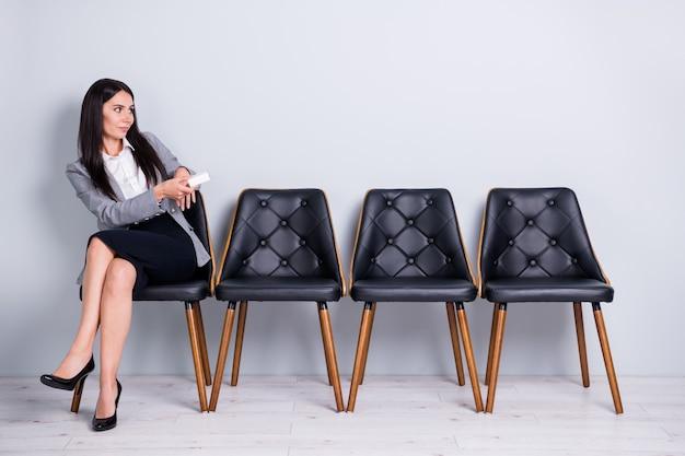 그녀의 초상화는 의자에 앉아 눈에 보이지 않는 클라이언트 파트너에게 작은 상자를 주는 멋지고 우아하고 똑똑한 여성 영업 관리자의 초상화입니다. 파스텔 회색 배경