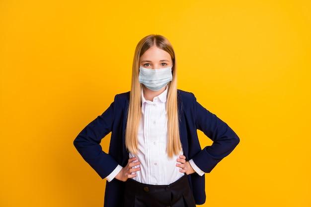Портрет ее она красивый привлекательный контент здоровый длинноволосый школьник в марлевой маске безопасности руки на бедрах mers cov профилактика изолированный яркий яркий блеск яркий желтый цвет фона