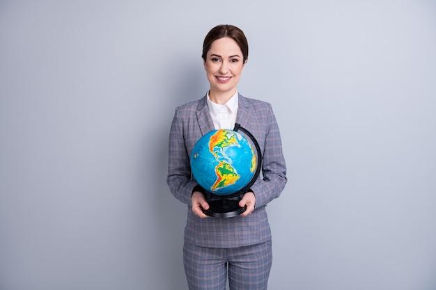 Портрет ее она красивый привлекательный контент профессиональный опытный веселый учитель-специалист, держащий в руках сферический глобус, преподавание изолированного на сером пастельном цветном фоне