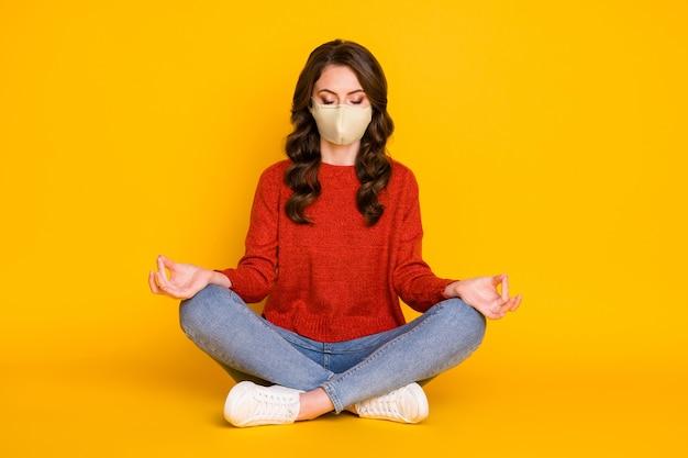 그녀의 초상화는 밝고 빛나는 노란색 배경에 격리된 명상을 하는 연꽃 위치에 앉아 있는 매력적인 꿈꾸는 집중된 물결 모양의 머리 소녀가 의료용 마스크를 쓰고 있는 모습입니다.