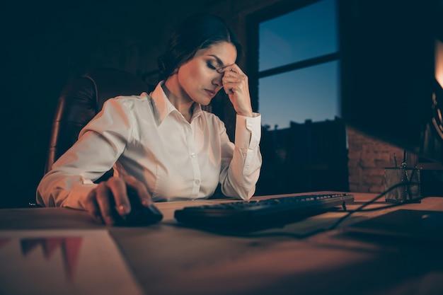 Портрет ее красивой привлекательной измученной бизнес-леди, агент, брокер, топ-менеджер, владелец рекламного агентства, трудолюбивый, страдающий от головной боли ночью, темное рабочее место, станция, в помещении