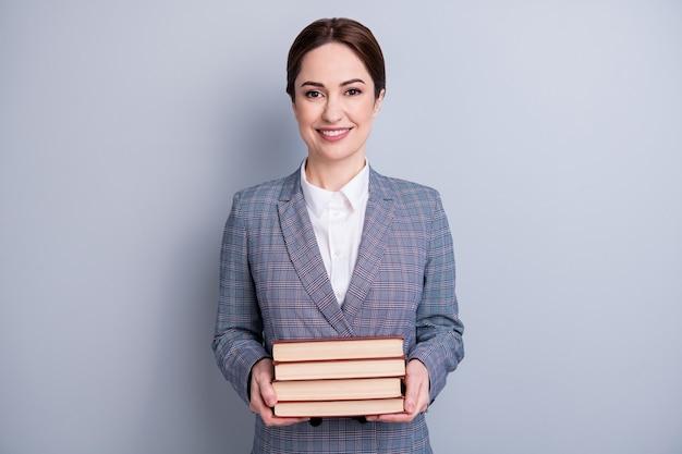 Портрет ее красивой привлекательной опытной знающей интеллектуальной веселой учительницы-библиотекаря в повседневном клетчатом костюме, держащей в руках литературу, изолированный серый пастельный цвет фона